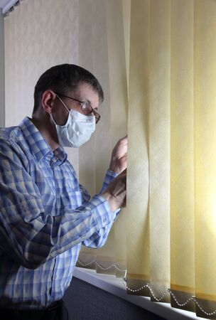 Man in a medical face mask looks out the window through the blinds. Quarantine during an epidemic. Afraid to go out Фото со стока
