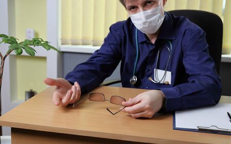 A doctor in a medical mask on his face explains something to the patient. He sits at the table and gestures to the problem. Focus on the hands