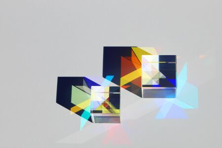 Two x-cubes cast shadows and create a colored pattern from the spectrum of light on the surface of the paper on a gray background