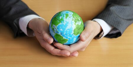 Two hands of a businessman support planet Earth. Green continents with blue oceans, concept for environmental protection