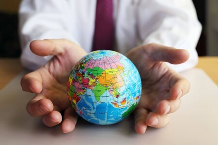 Man supports planet Earth to protect against dangers. Globe side with Asia in the foreground. Countries represented with approximate borders