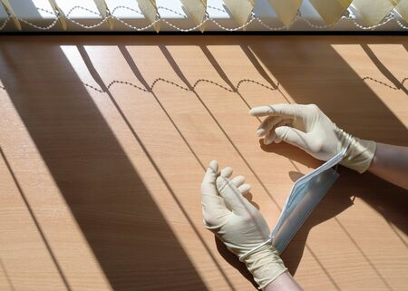 Symbol of imprisonment during quarantine. Hands in medical gloves are focused on freedom, where sunlight passes through the blinds in the form of a lattice