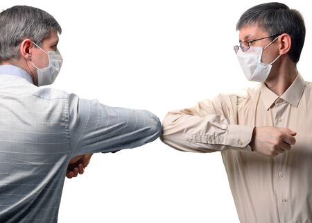 Two people greet elbows bump. New style of greeting during the spread of coronavirus. Isolated on a white background Foto de archivo