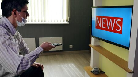 Person stays at home and waits for what news will be broadcast on television in connection with the pandemic situation. The inscription NEWS in large letters is visible on the screen