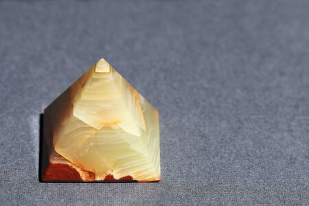 Onyx marble in the form of a pyramid on a gray texture surface with copy space