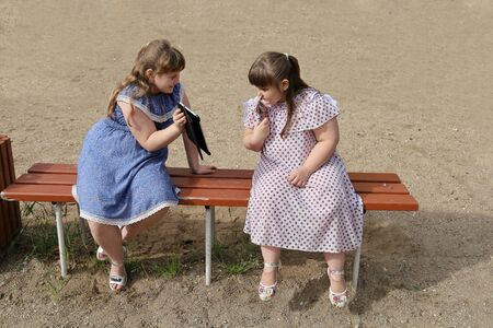 Chubby girl shows something interesting to another girl on her electronic tablet. Overweight children move a little and are only interested in their devices. Sand background with copy space