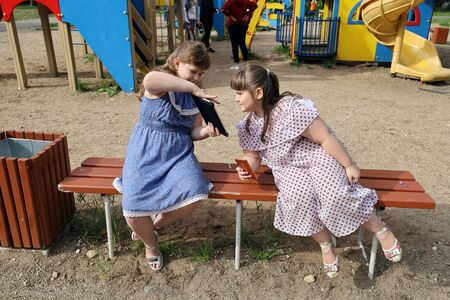 Little chubby girl with a satisfied smile shows the other girl something on her tablet. Overweight children do not play on the playground, but are busy with electronic devices Archivio Fotografico