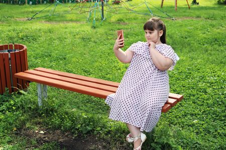 Little plump girl takes selfie on smartphone. She sits on a bench in a deserted park and does not want to play outdoor games. The problem of excess weight in children