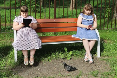 Two chubby young girls are bored on a park bench. They sit at a social distance after quarantine and do not communicate with each other, but are busy with their electronic devices Archivio Fotografico