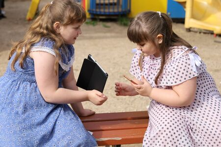 Two little plump girls exchange data from their electronic devices. They communicate sitting on a bench on the playground, but do not play outdoor games. The problem of overweight children and addiction to devices Archivio Fotografico
