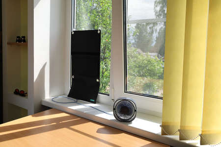 Solar charger on the suction cups attached to the glass of the window generates energy and powers the portable desktop fan, which is located on the windowsill and blows into the room