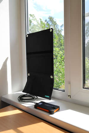 Portable solar charger on the suction cups attached to the glass of the window generates energy and charges the powerbank on the windowsill. Sunny day, vertical format Zdjęcie Seryjne