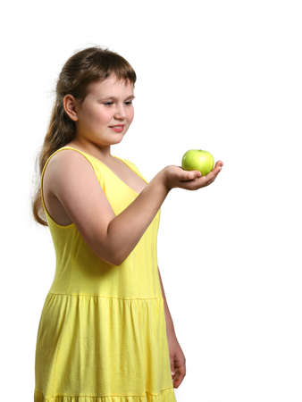 Chubby smiling girl in yellow sundress stands and holds green apple in her right hand and looks at it. On white background in vertical format