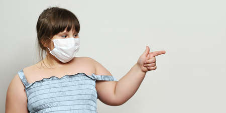 Plump little girl in medical face mask looks towards an empty space and points her finger at something there. Neutral gray background with copy space