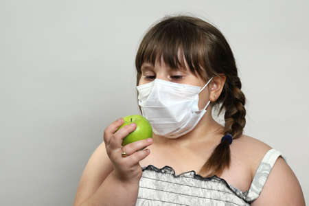Little plump girl in medical face mask holds green apple and brings it to her face. She thinks how to eat it. Safety after quarantine and during infections. Close-up on gray background with copy space