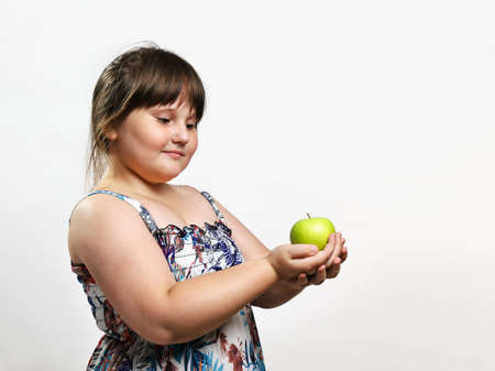 Little chubby smiling girl holding green apple in her hands. Half-length portrait on light background with copy space