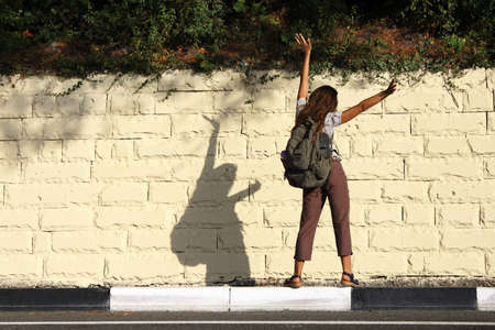 Young woman tourist with backpack stands with her back to the road at the edge of the curb and waving her arms, looking at her shadow on light stone wall