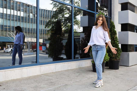Young beautiful woman with long hair and in casual clothes stands near glazed building, where you can see her reflection and the city street