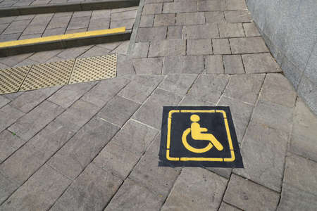 Yellow sign denoting ramp for the disabled on concrete street tile at the beginning of the rise