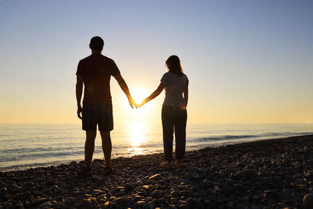 Loving couple hold hands in the rays of the setting sun on the seashore. Concept of love and happiness together Imagens