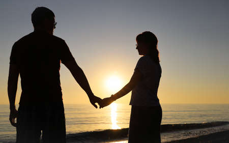 Silhouette of happy couple holding hands on the background of the setting sun on the seashore