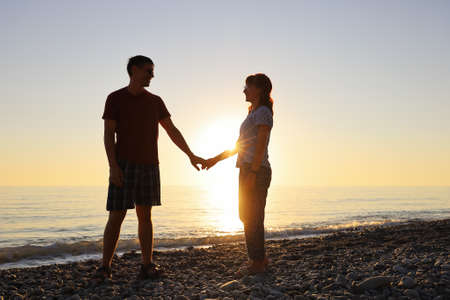 Lovers smile and look at each other in the rays of the setting sun on the seashore. Happy relationship together