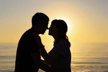 Silhouette of couple in love who touch each other with their noses against the backdrop of the setting sun. Happy relationship concept with copy space Imagens