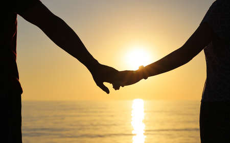 Silhouette of couple holding hands against the setting sun. Strong relationship concept Imagens