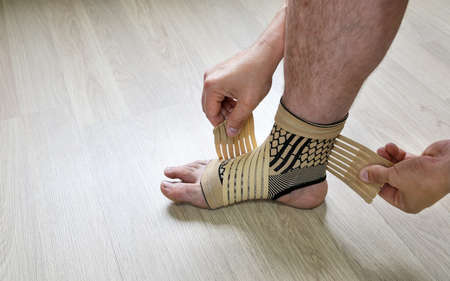 Human hands fix an elastic bandage sock to protect the ankle of the leg from sprains, close-up Banque d'images