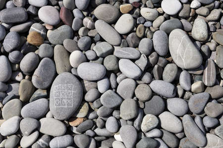 Tic-tac-toe on the sea shore pebbles in flat lay. Outdoor play with the result of draw