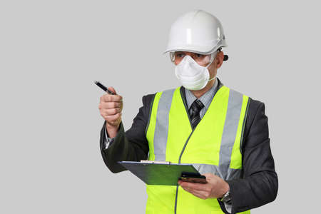 Man in suit is wearing reflective vest, mask and hard hat. He inspecting, holds clipboard and points with pen at something. Isolated on gray background