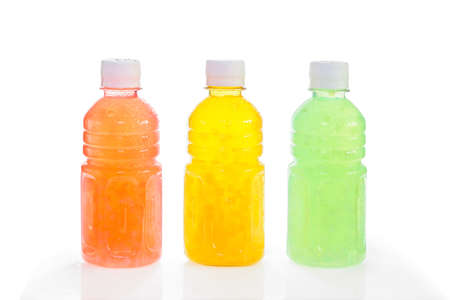 Three plastic bottles with fruit drink of different colors with water droplets freshness, isolated on white background Stockfoto