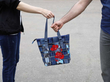 Men's hand take away jeans bag from woman, close-up