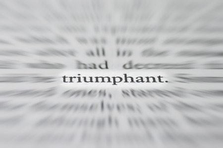 triumphant: macro photograph of the word triumphant- concept