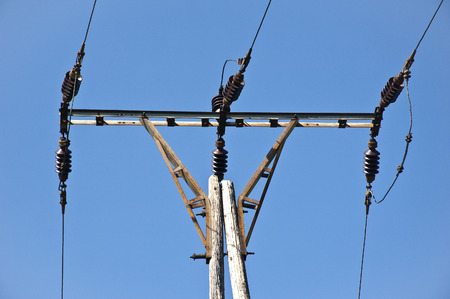 electrochemical: old wooden electricity pole with blue sky