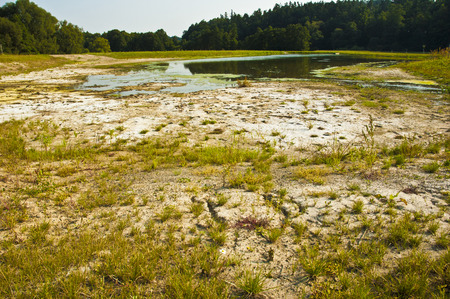 Polluted water and cracked soil of dried out lake during drought.  photo