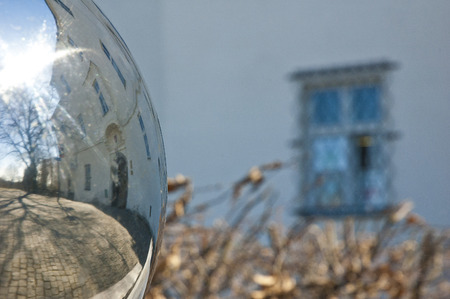 mirroring: Sphere mirroring castle with defocused barred window and bushes.