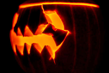 A burning head carved from a pumpkin with an ominous smile for the holiday of Halloween. Imagens