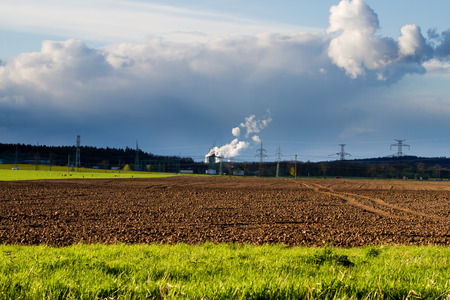 cultivated land: Nuclear power station with the cultivated land in the foreground. Dramatic sky with smoke.