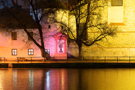 budejovice: Night architecture in the city. Old church on the bank of river. Czech Budweis.