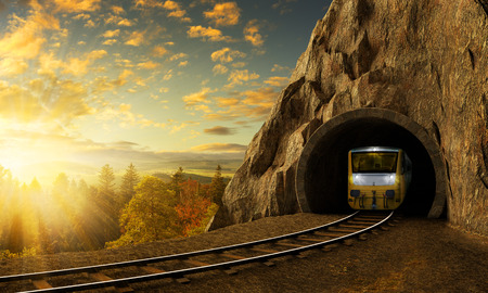 Mountain railroad with train in tunnel. Sunset landscape under the big rock. Stock Photo