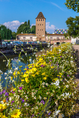 Medieval bridge Ponts Couverts in Strasbourg behind the flower decoration.