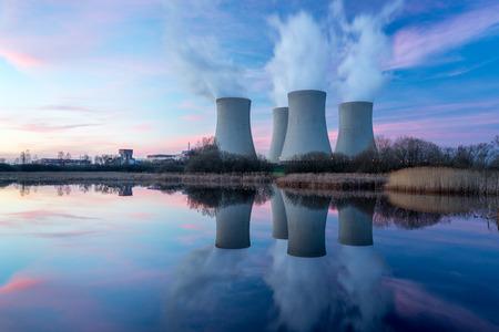 Kerncentrale na zonsondergang. Schemer landschap met grote schoorstenen. Stockfoto