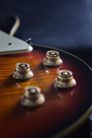 sunburned: Detail of electric guitar on black background