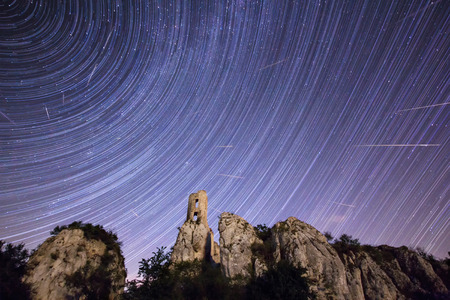 meteor: Star trails with meteor shower above old castle ruin Stock Photo