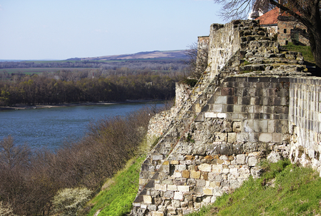 stilish: Bit ruined fortification located on the top of the mountain above the Danube river. Part of the picture takes a nice view of the river, hills and blue sky. Estergom. Hungary. Stock Photo