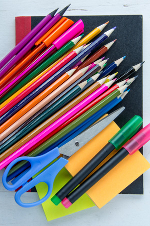 post it notes: Pens, pencils, scissors and post it notes placed on black note book Stock Photo