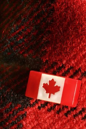 Canadian stick pin on red woolen plaid material. Signs and symbols of Canadian pride. Pin represents Canadas flag. Woolen material is a symbol for the cold winter in Canada. Up close macro photo. photo