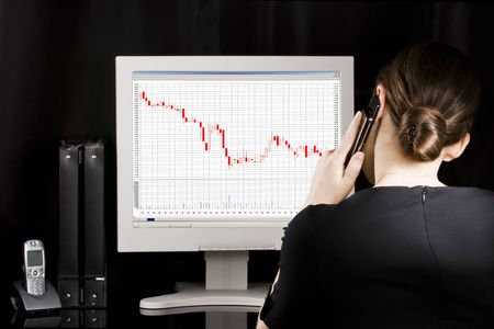 Businesswoman at her workplace. Business graphs going down on computer monitor  photo