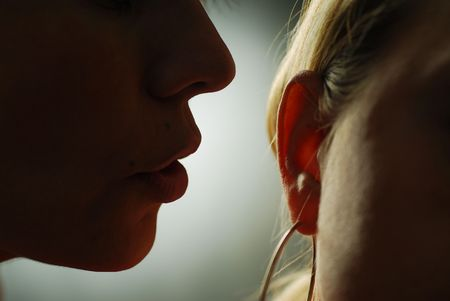 telling: Someone whispering to ones ear Stock Photo